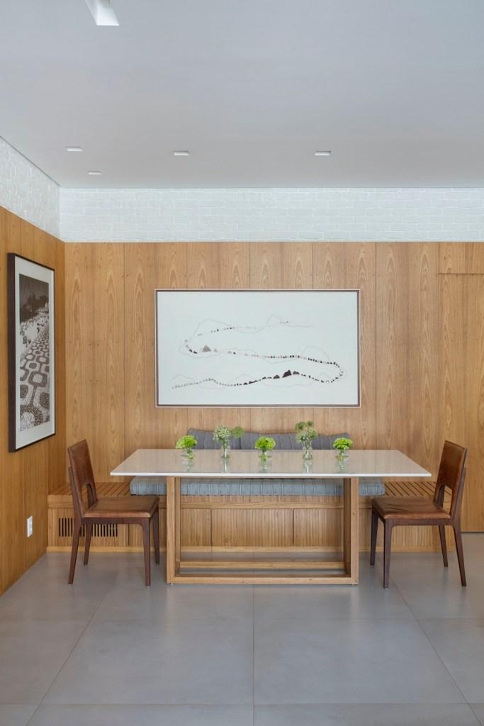 Sala de jantar com paredes revestidas de madeira
