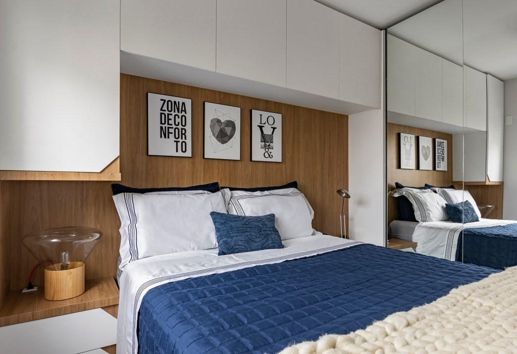 """Quarto com cama de casal e colcha azul escura. Parede em madeira e estantes brancas na lateral e acima da cama. Três quadros onde le-se """"zona de conforto"""" """"love"""" e um com um coração"""