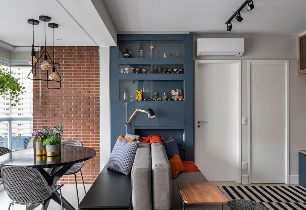 Apartamento integrado. Sofá cinza à direita e mesa de jantar preta à esquerda. Estante azul escuro com bonecos funko e garrafas de bebida.