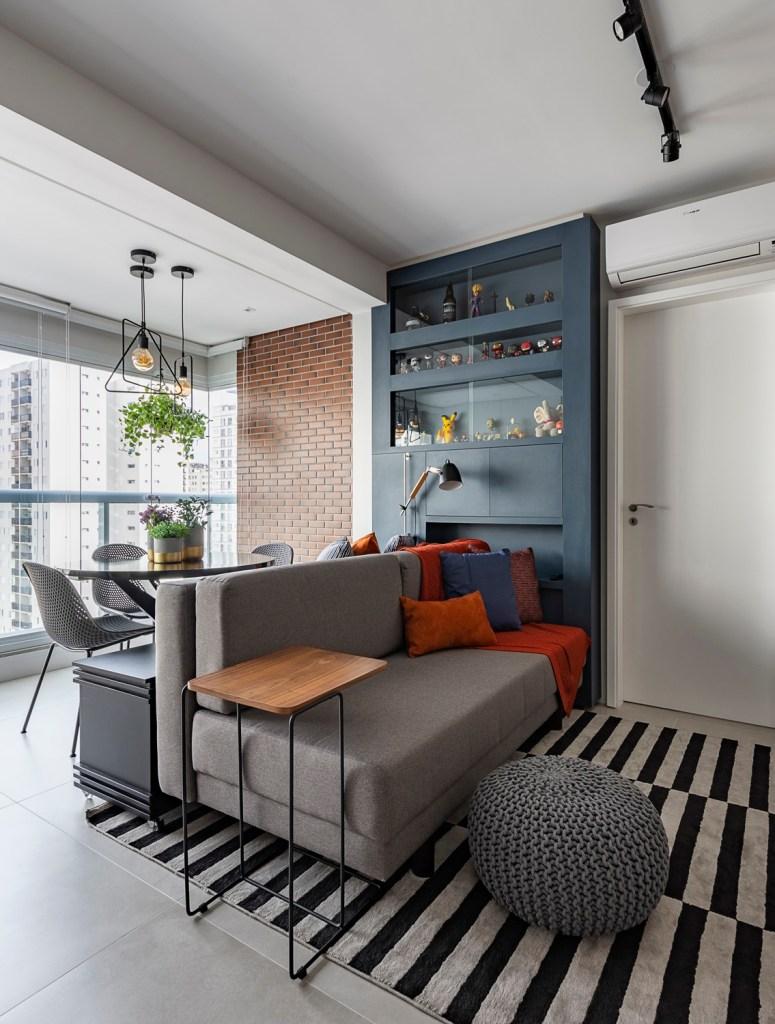 Sofá cinza com travesseiros laranja. Estante azul escura com bonecos. Varanda integrada com mesa de jantar.