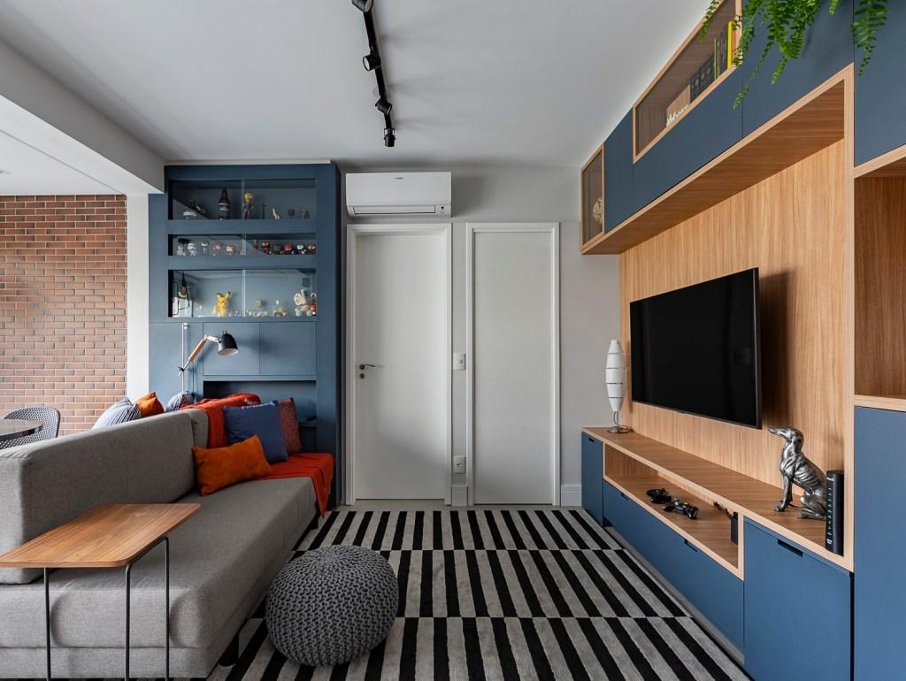 Estar com sofá cinza e tapete preto e branco listrado. Hack de madeira com televisão. Ao fundo, estante azul com bonecos e garrafas de bebida