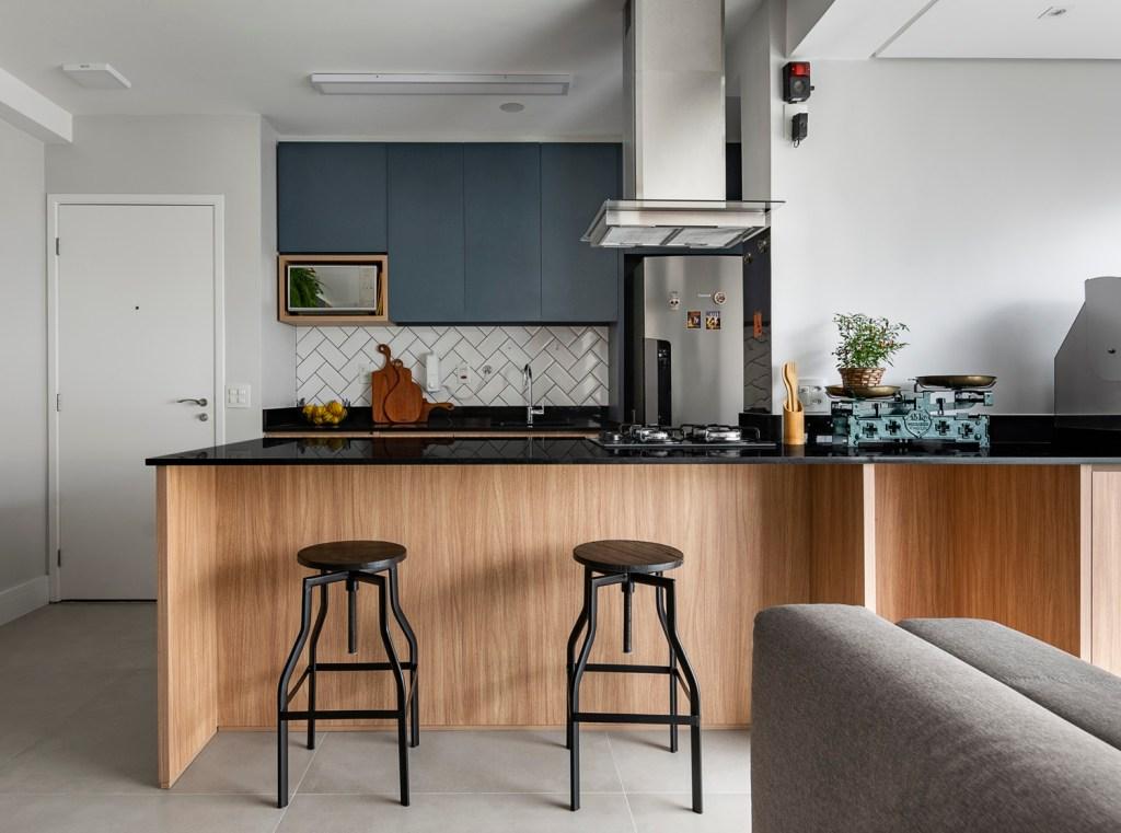 Cozinha integrada com bancada em madeira com tampo preto. Dois bancos pretos. Estante em marcenaria azul escura