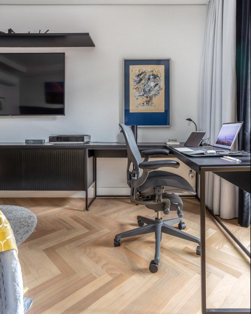 """Homa office no quarto. Mesa em formato de """"L"""" com notebook e cadeira de escritório. TV à esquerda."""