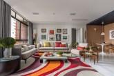 Sala de estar com tapete cinza com padrões curvos vermelhos, laranjas e roxos. Dois sofás neutros com almofadas coloridas. Janela à esquerda. Área revestida de madeira à direita com mesa pequena de dois lugares. Ao fundo, quadros na parede.
