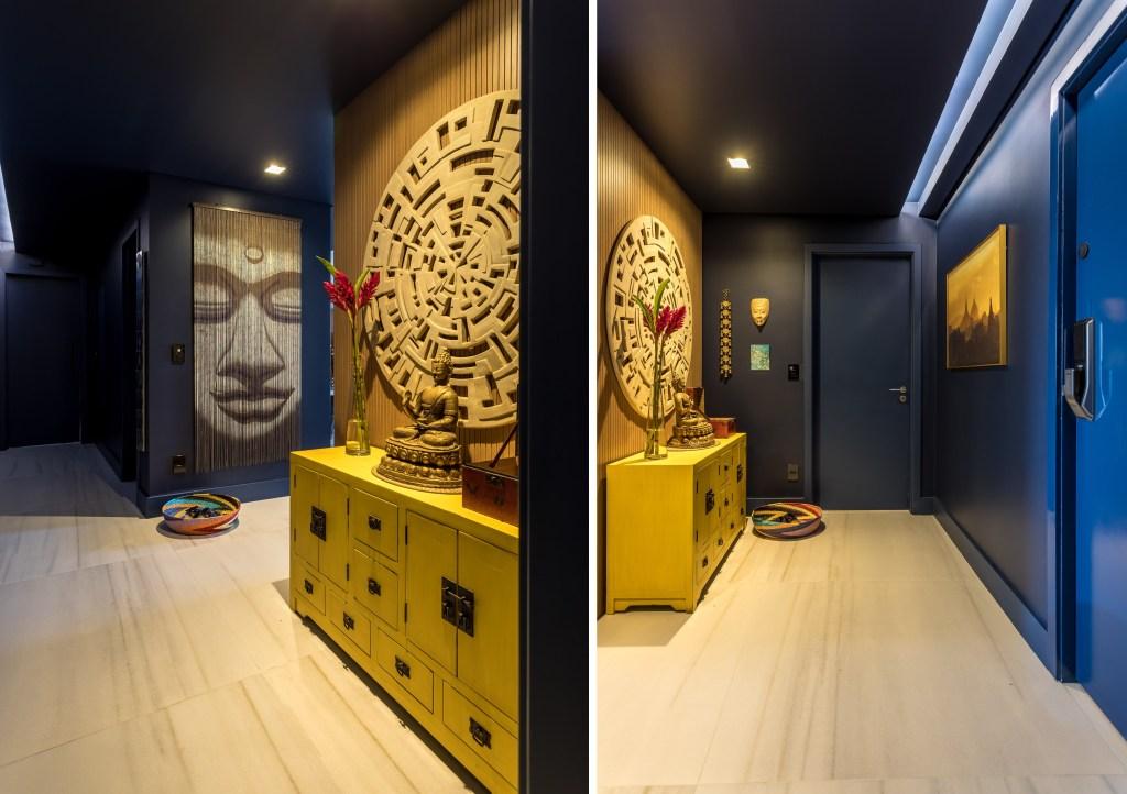 Hall de entrada com piso em madeira clara. Aparador amarelo e paredes azul escuro. Estátua de Buda e outros objetos asiáticos nas paredes