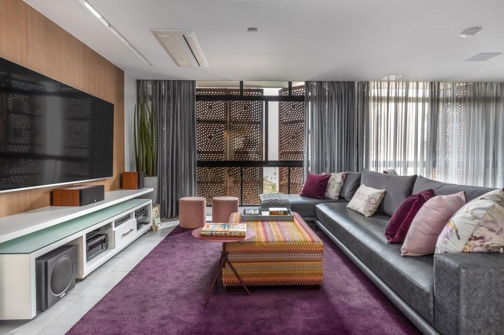 Sala de tv com tapete roxo e sofá cinza. Almofadas roxas e lilás. Parede da tv revestida com madeira. Hack branco e mesa de centro puff colorido