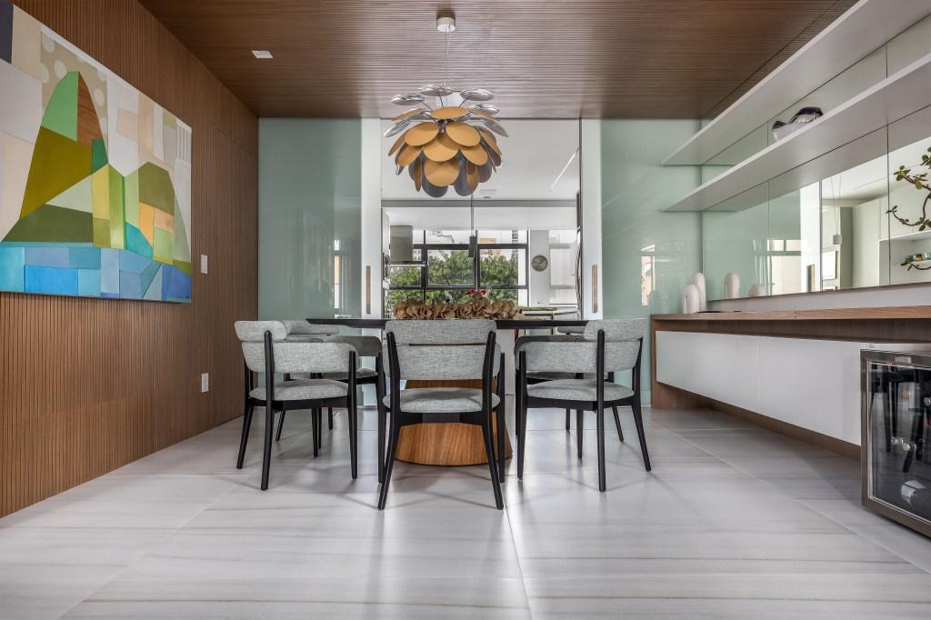 Sala de jantar com piso claro. Parede e teto em madeira. Mesa circular com cadeiras pretas de encostos cinzas. Lustre acima.