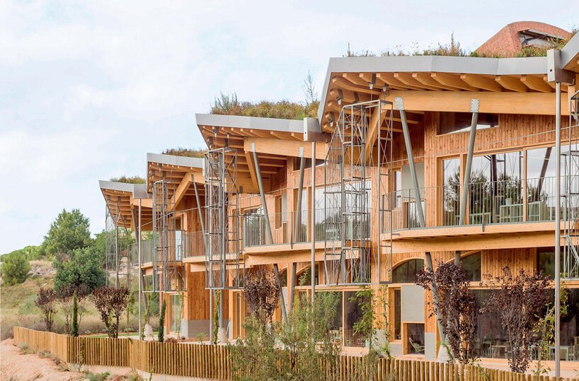 Escola feita de tijolo e madeira, com pé direito triplo e janelas de vidro