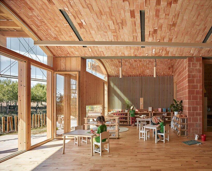 Sala de aula ampla, com janelas e porta de vidro; mesas e brinquedos estão à disposição das crianças na Escola Montessoriana