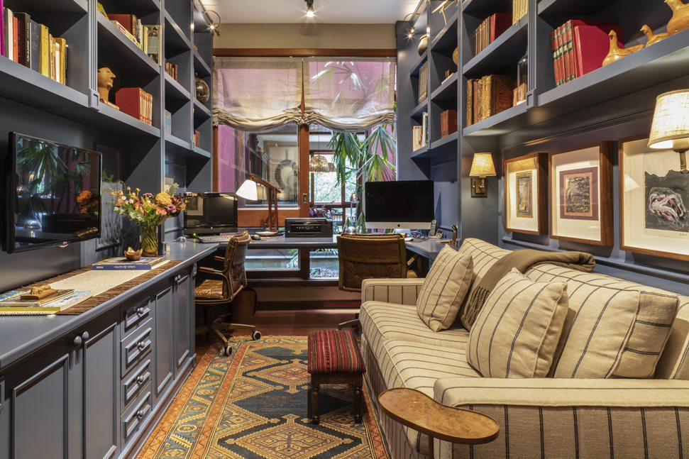 Escritório com estantes azuis cobrindo as paredes. Livros nas prateleiras. Sofá branco e listrado na frente da tv. Ao fundo, mesa com dois computadores e cadeiras de escritório