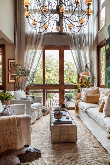 Sala de estar com pé direito duplo. Lustre rústico. Sofás e poltronas brancos com almofadas brancas e amarelas. Porta de vidro levando à deck externo