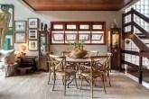 Sala de jantar com tapete de linho. Teto em madeira. Janelas em madeira ao fundo. No centro, mesa de jantar com cadeiras de madeira.