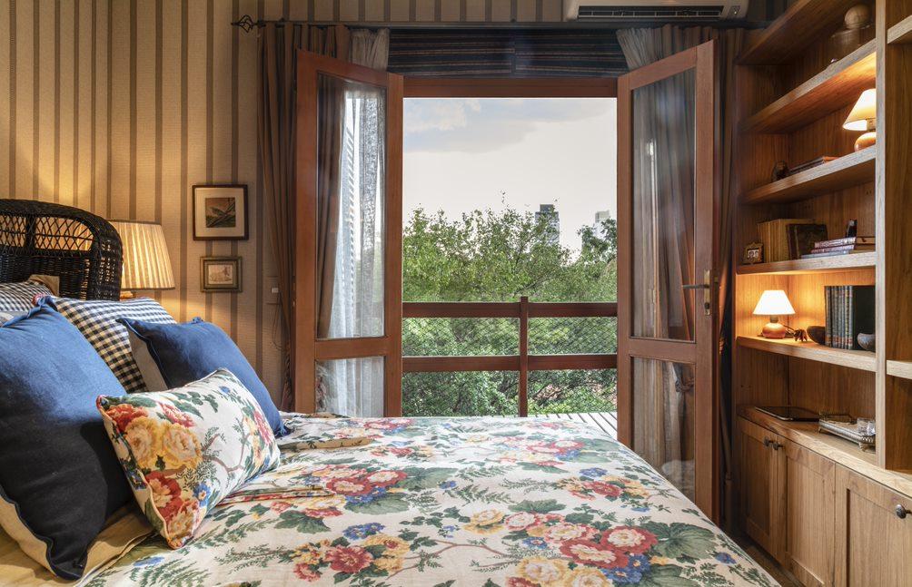 Cama de casal com colcha florida e travesseiros azuis escuros. Estante em madeira na frente da cama. Ao fundo, papel de parede listrado e porta de vidro levando à varanda.