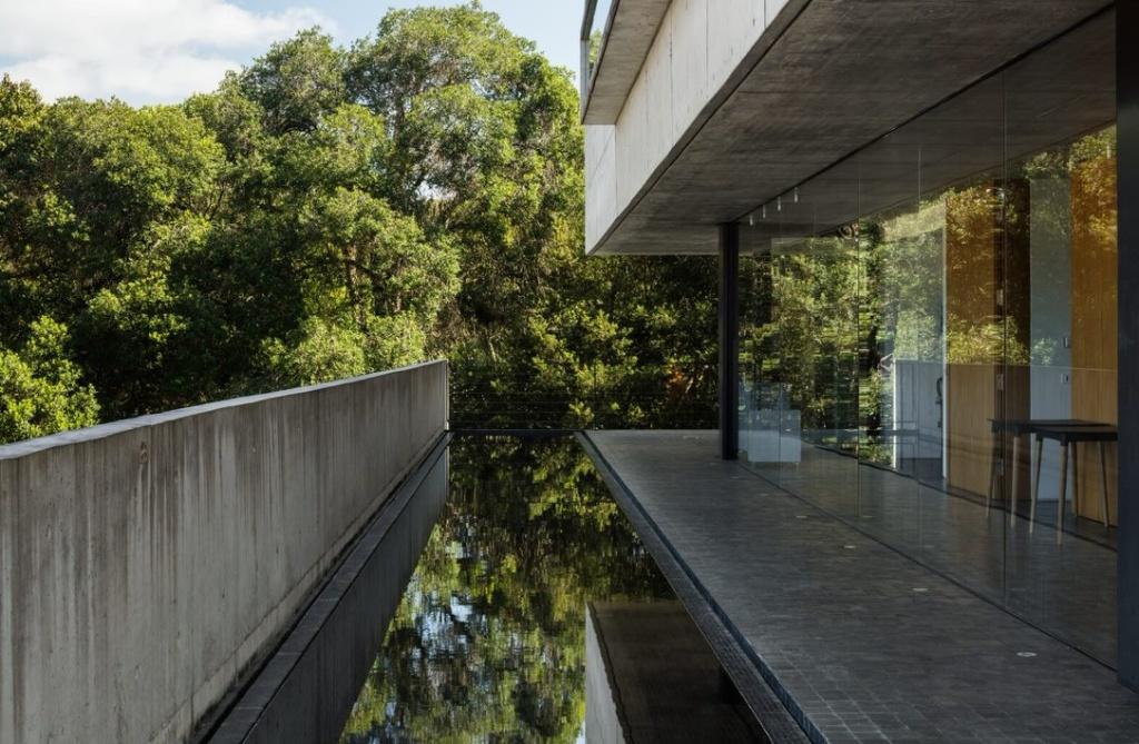 Casa de concreto com espelho d'água e parede em vidro e bosque ao fundo
