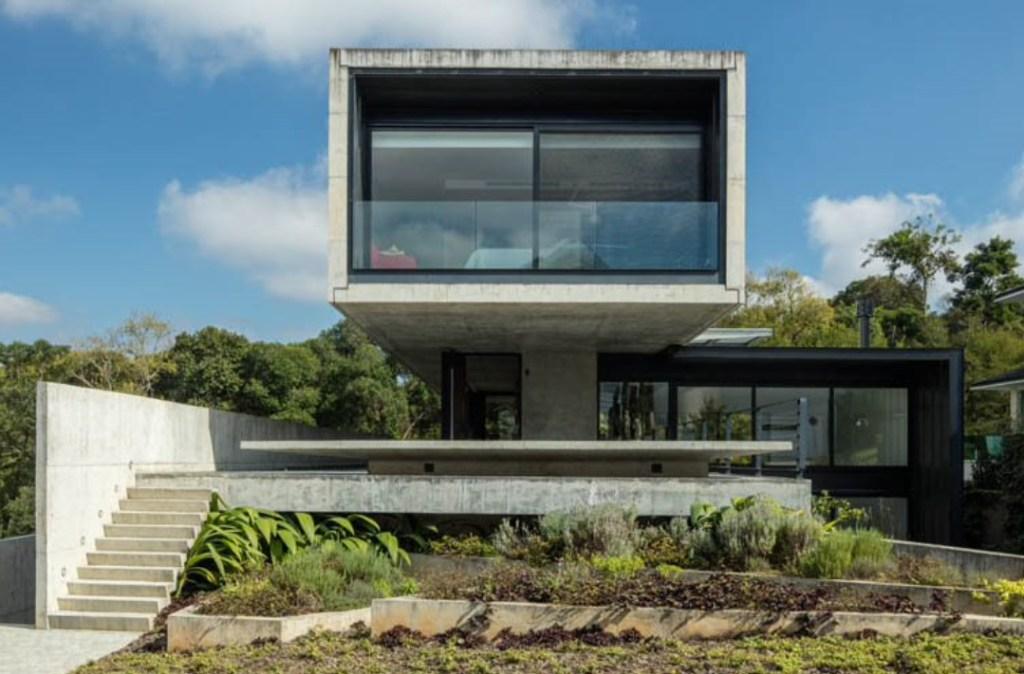 Casa composta por dois blocos em concreto encaixados perpendicularmente