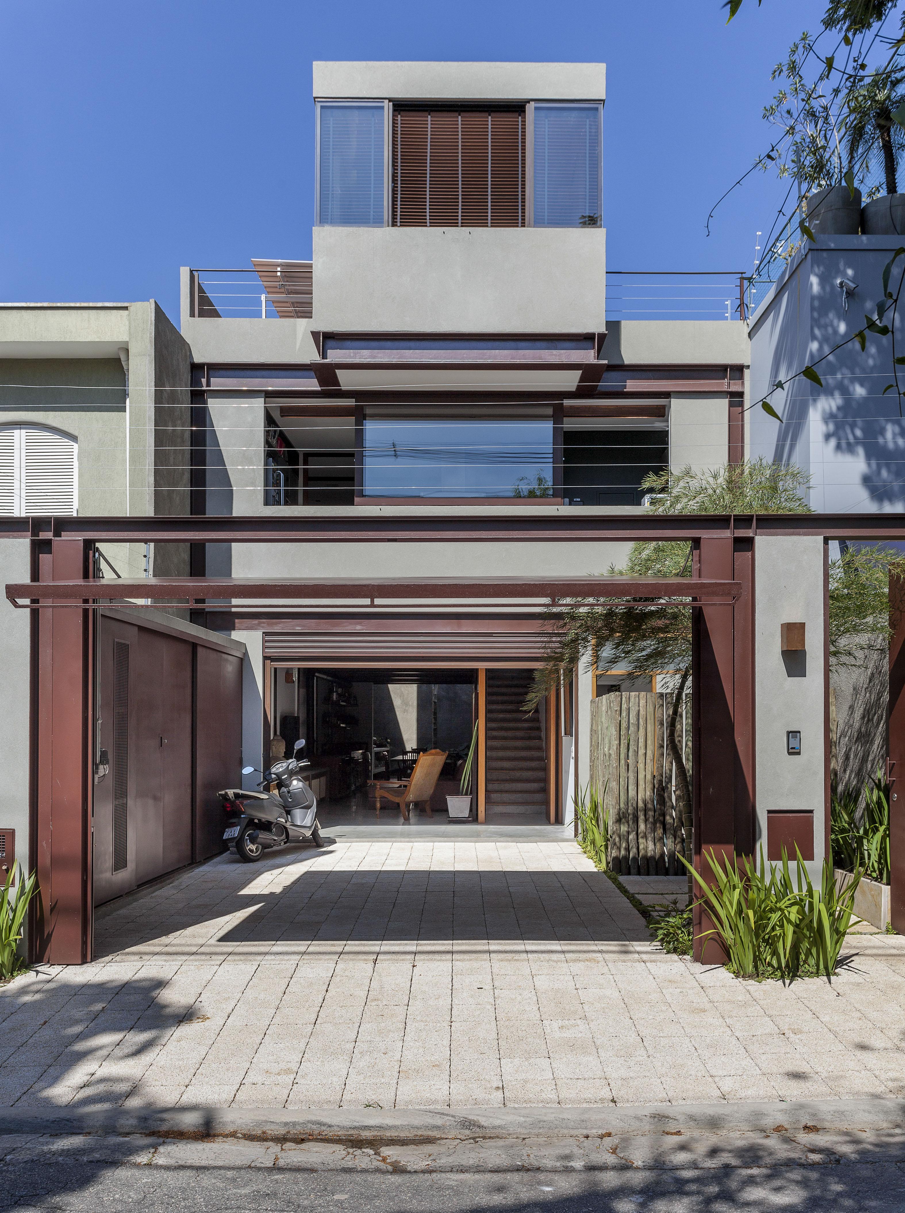 Casa de três andares aproveita o terreno estreito com estilo industrial