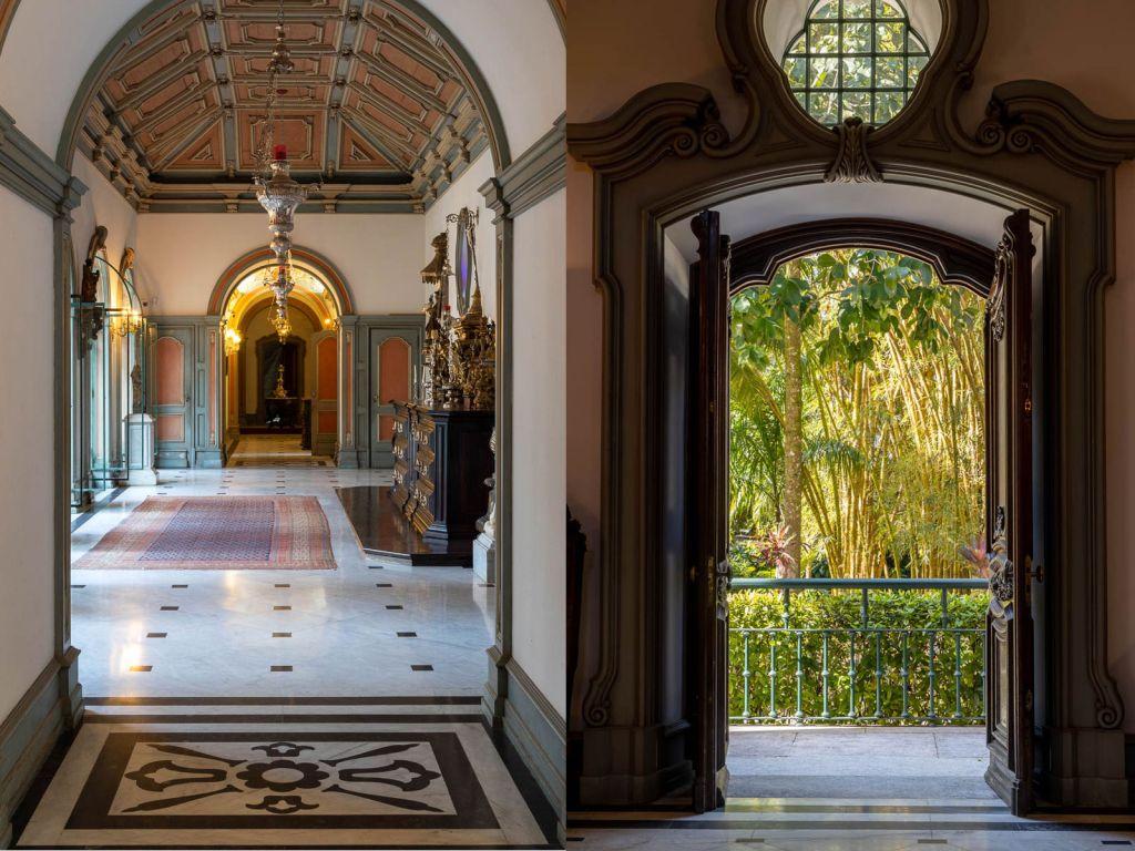 À esquerda, corredor com piso com mosaicos, teto adornado e móveis em madeira com ornamentos. À direita, porta em madeira com ornamentos que se abre para um jardim verde