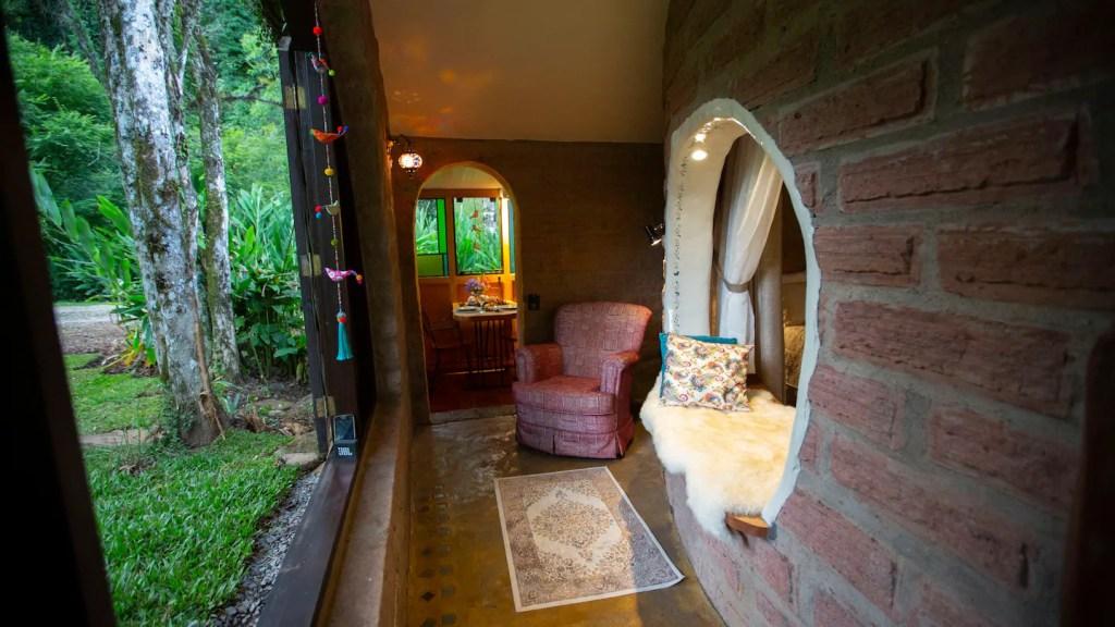 Hall de entrada de tijolos laranjas, com uma poltrona vermelha, um tapete estampado e um peitorial da janela arredondado com almofadas para sentar.