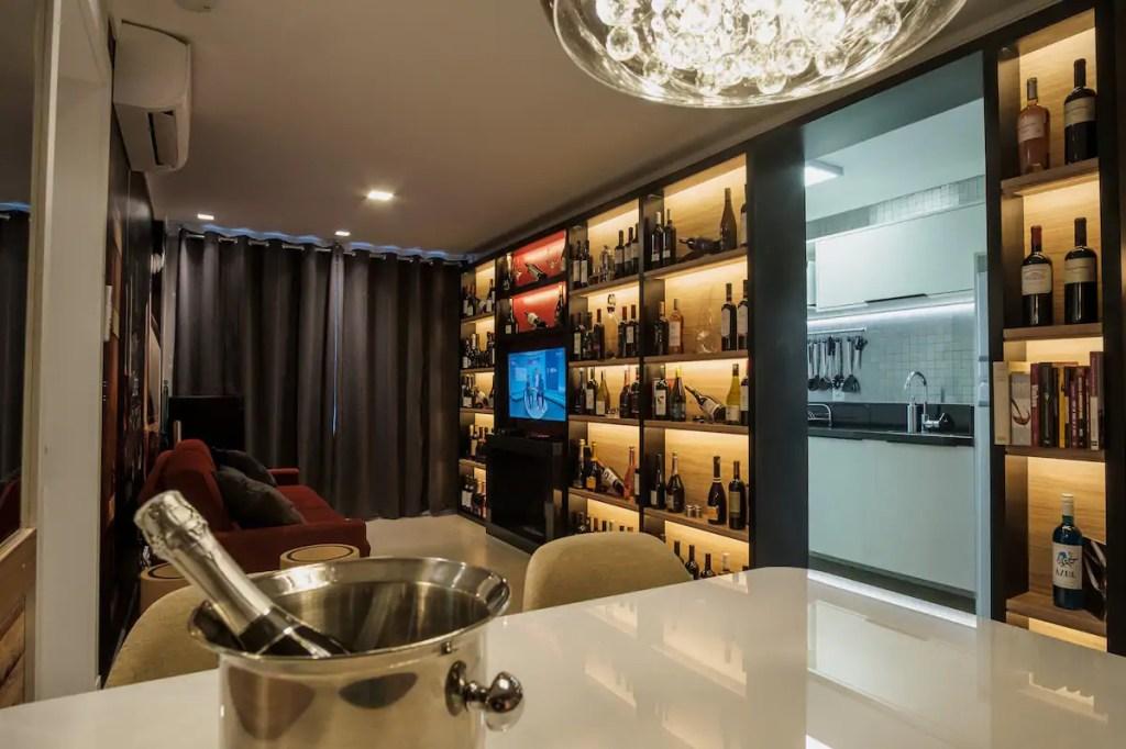 Sala de estar, com estante cheia de vinhos nos nichos. No centro, uma TV é emoldurada por eles.