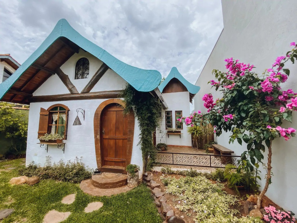 Casa de conto de fadas com parede branco, teto triangular de madeira, porta e janela com batente arredondado