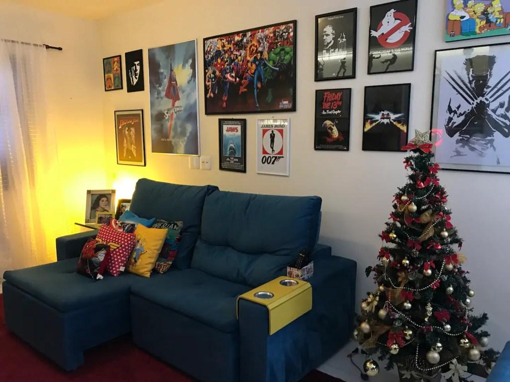Sala com sofá azul com parede decorada com quadros temáticos de super heróis em tamanho diferentes