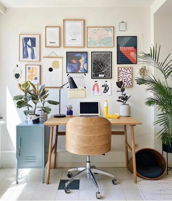 home office com cadeira e mesa em madeira. computador na mesa. Plantas em ambos os lados. Quadros diversos na parede