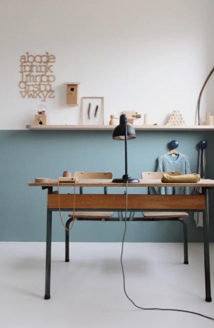 Home office com parede meia colorida em azul. Quadros na prateleira de madeira que marca a divisão entre a parte azul e a parte branca da parede. Mesa em madeira.