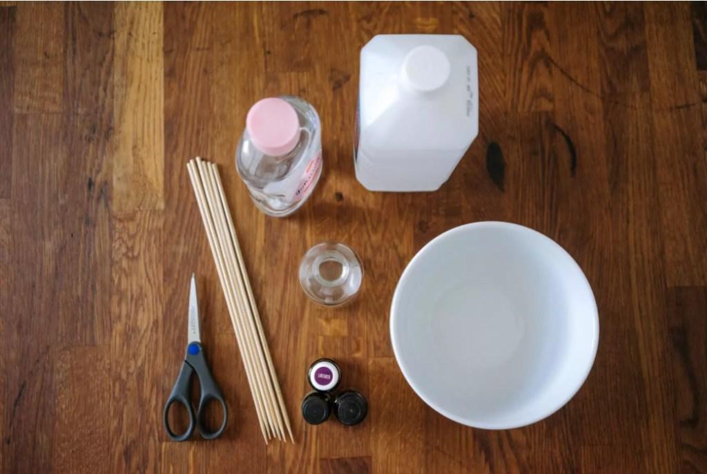 Mesa de madeira com produtos para fazer aromatizador.  Tesoura, varetas, alcool, tigela, frasco de vidro e óleos. Todos vistos de cima.