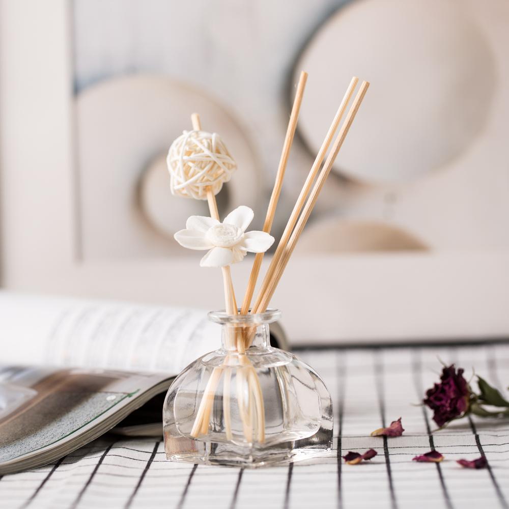 Frasco de vidro aromatizador com base quadrada e lados arredondados em cima de toalha branca com padrão quadriculado preto. Três varetas de madeira saindo do frasco. Uma vareta com flor branca e outra com bolinha branca.