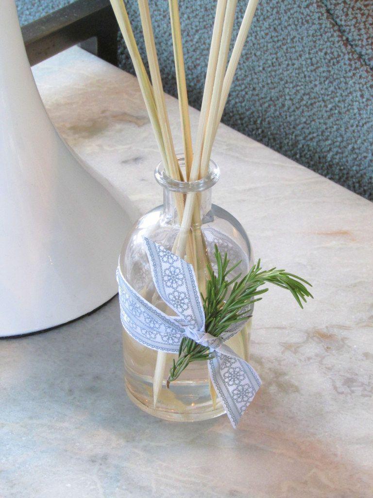 Difusor com frasco transparente e varetas de madeira. Fita roxa amarrada no meio do frasco com um ramo de alecrim preso nela