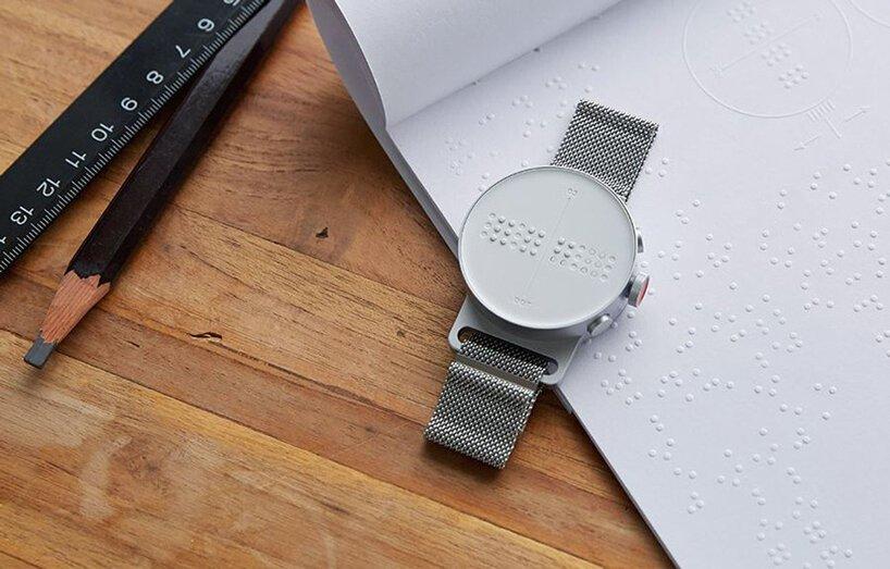 Dot watch sobre mesa de madeira e cadeno braille. No canto superior esquerdo, um lápis preto e uma régua