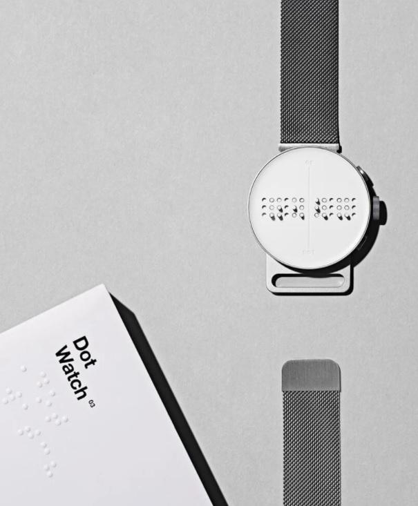 Dot Watch com a pulseira aberta em uma das extremidades em fundo cinza. No canto inferior esquerdo, manual do relógio em braille