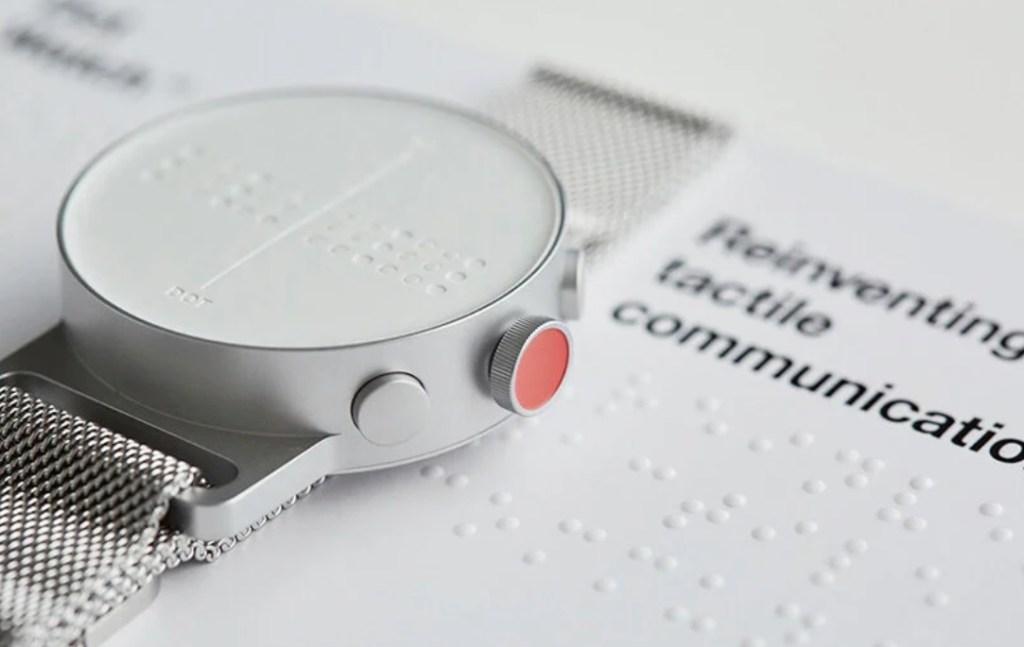 Detalhe do mostrador do Dot watch. Com manual em braille na mesa