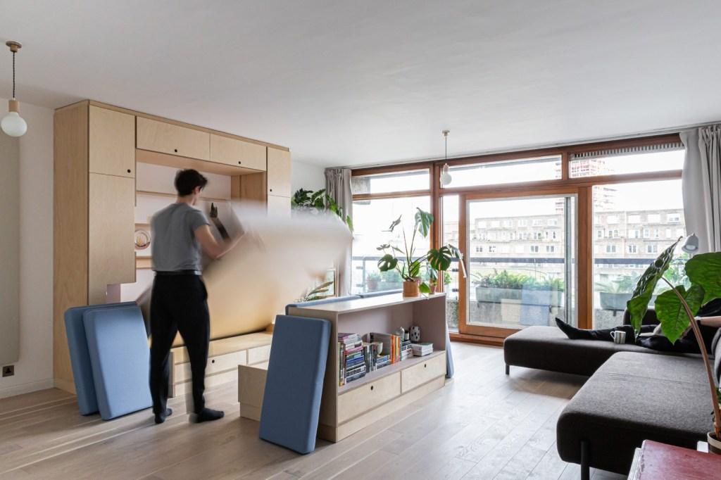 Flat com piso em madeira e grande janela. Homem abaixa colchão de móvel de madeira clara na parede.
