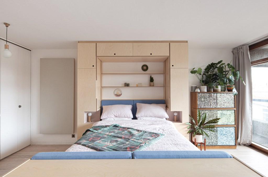 Cama de casal que sai do móvel na parede. Com o colchão abaixado, ela fica emoldurada por armários e prateleiras