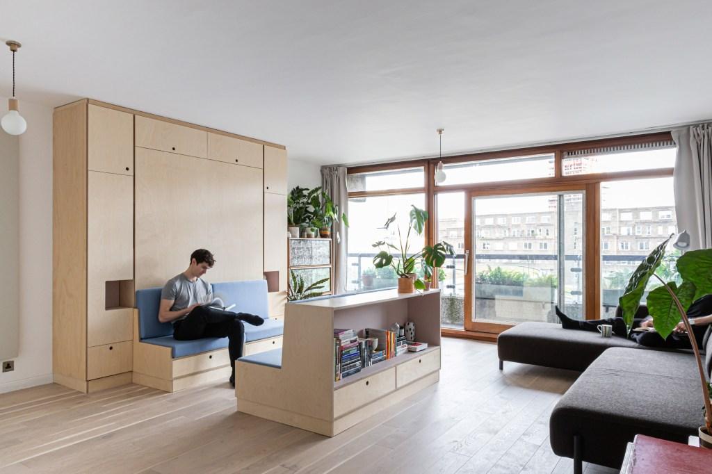 Homem sentado lendo em banco com almofadas azuis. O suporte do banco vem do móvel de madeira na parede