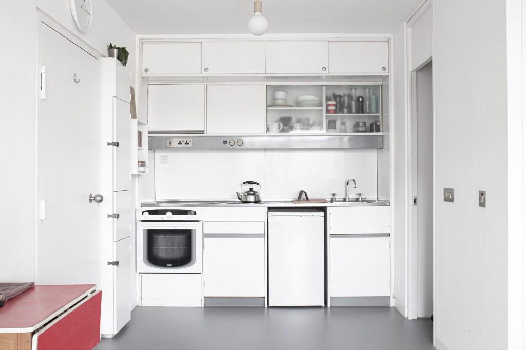 Cozinha com armários e eletrodomésticos brancos. Pequeno balcão vermelho no canto inferior direito.