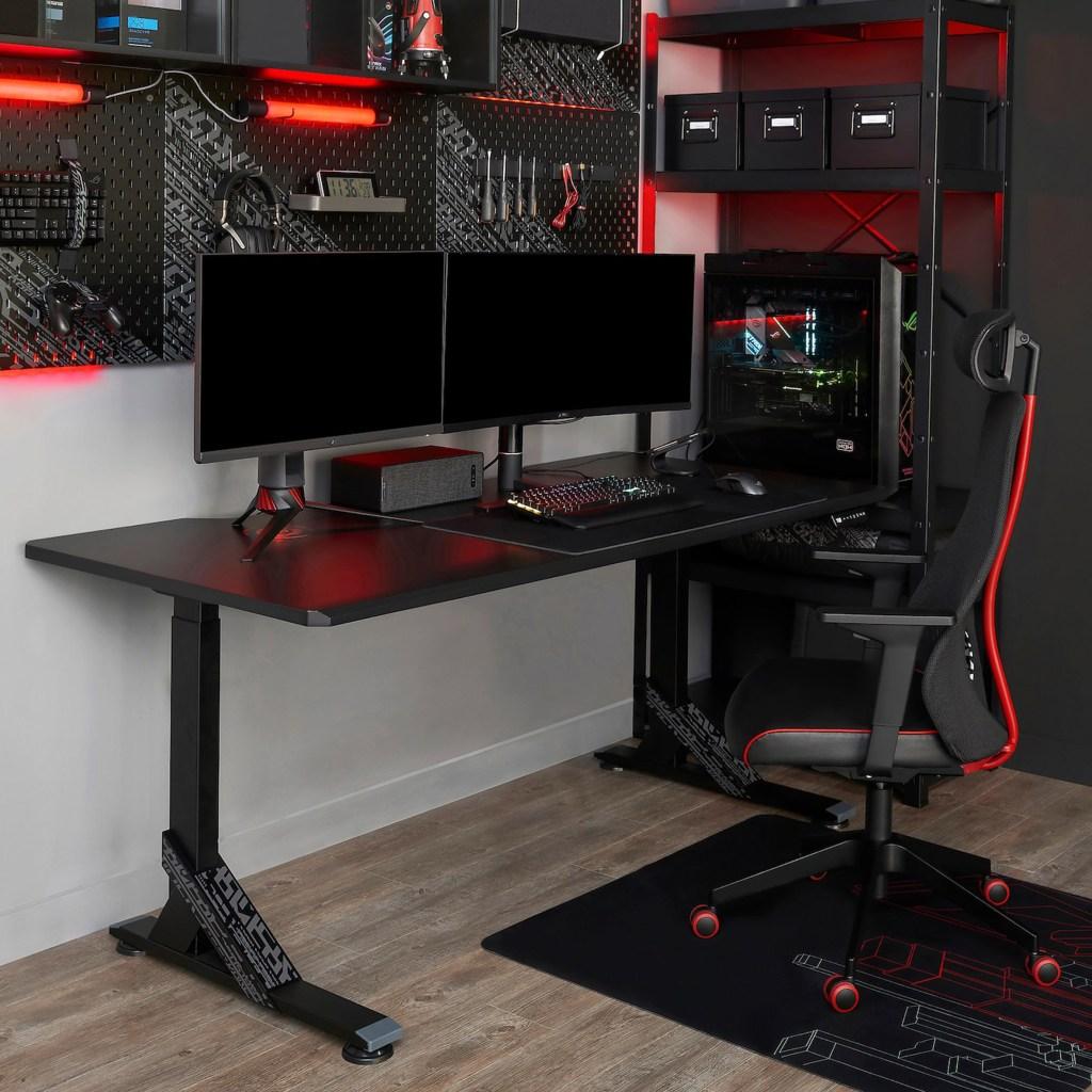Mesa preta com dois monitores de computadors. Na parede, um mural com acessórios, como fone, teclado e ferramenta. Na lateral, uma estante com a CPU. E uma cadeira gamer com detalhes vermelho.