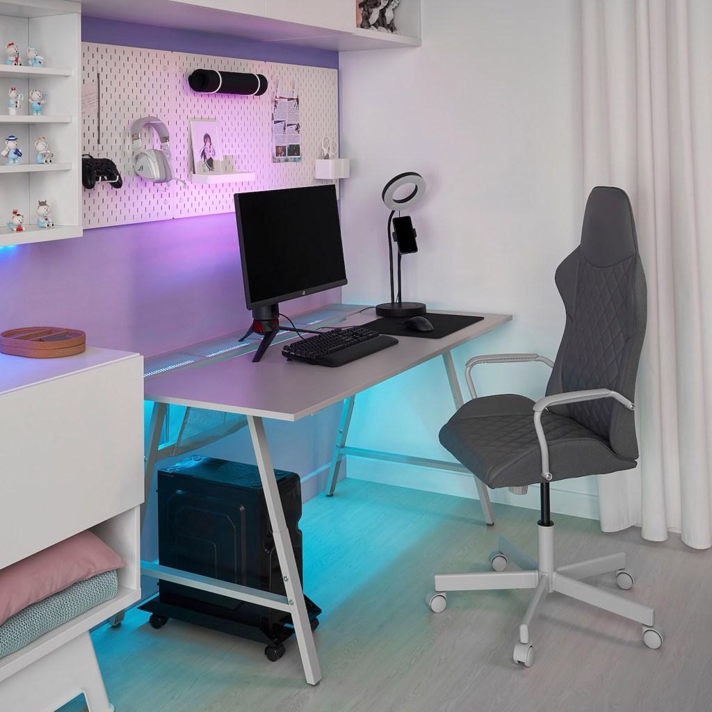 Mesa cinza, com luzes lilás na parte traseira superior e azul claro na parte inferior. Um monitor, telcado e mous sobre a mesa. Na parede, um mural branco com fone de ouvido, controle de video game e um porta retrato. A CPU fica no chão, do lado esquerdo da mesa, e a cadeira é cinza.