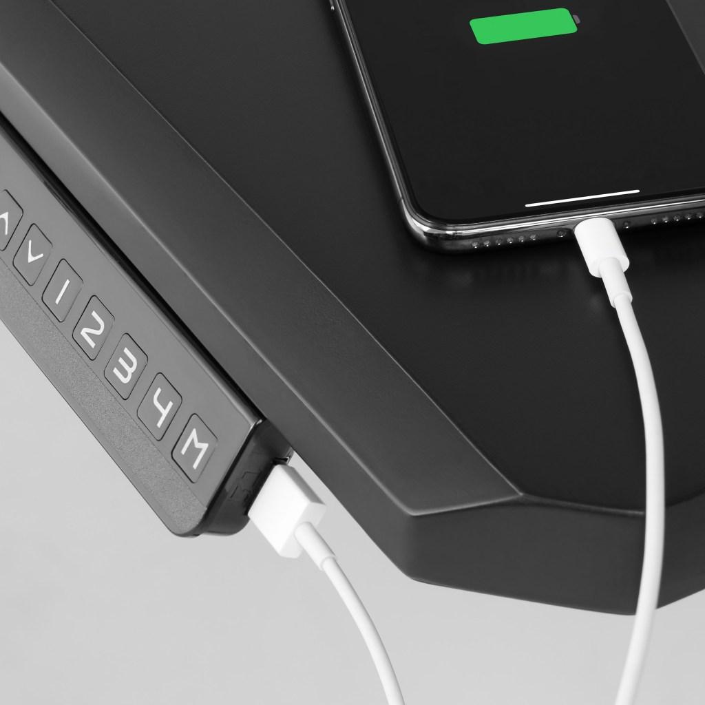 Lateral da mesa com a entrada USB com um fio branco conectado à ela e a um celular que está carregando