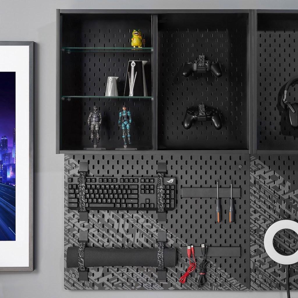 Um mural preto com teclado, mousepad e ferramentas presos a ele com fita. Acima, nichos estão decorados com figuras de ação e controle de video game