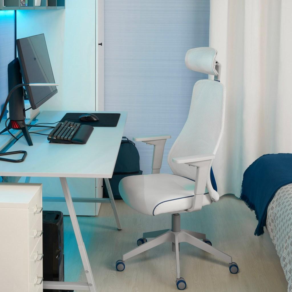 Mesa branca com luzes azul clara, um monitor teclado mouse e mousepad acima dele. Abaixo, do lado esquerdo, a CPU e de frente para ela, uma cadeira branca