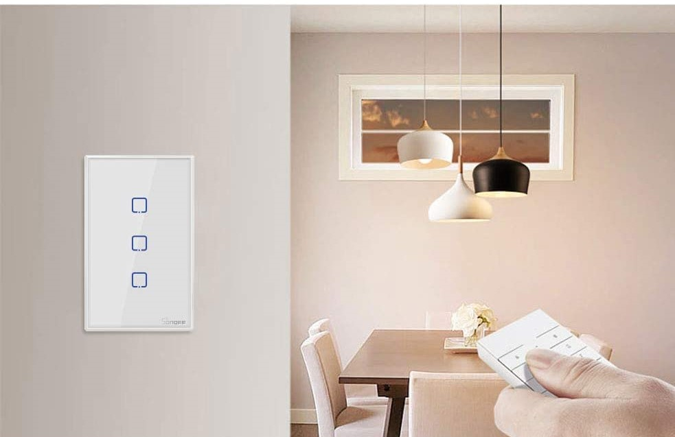 Interruptor WiFi branco em parede clara. Ao fundo, mesa em madeira com cadeiras claras e três luminárias pendentes