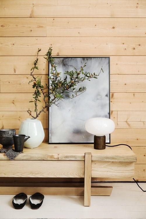 Hack de madeira com parede em madeira ao fundo. Quadro cinza e branco apoiado sobre o hack. Abajour pequeno na frente do quadro. Vaso com galho com folhas à esquerda junto de um jogo de chá estilo japonês