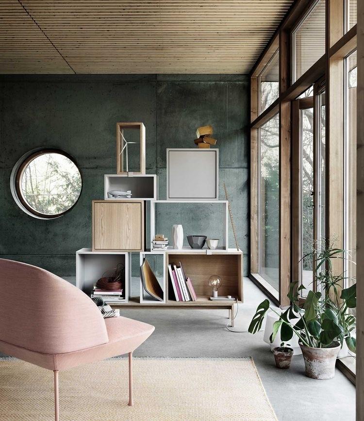 Sala com parede verde queimada e janela. Poltrona rosa clara em primeiro plano e estante de nichos de diversos tamanhos em madeira empilhados ao fundo