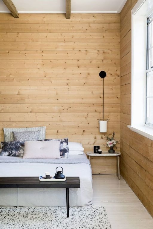 Quarto com parede de madeira e cama de casal branca com quatro almofadas. Luminária pendente pequena do lado direito funcionando como abajour