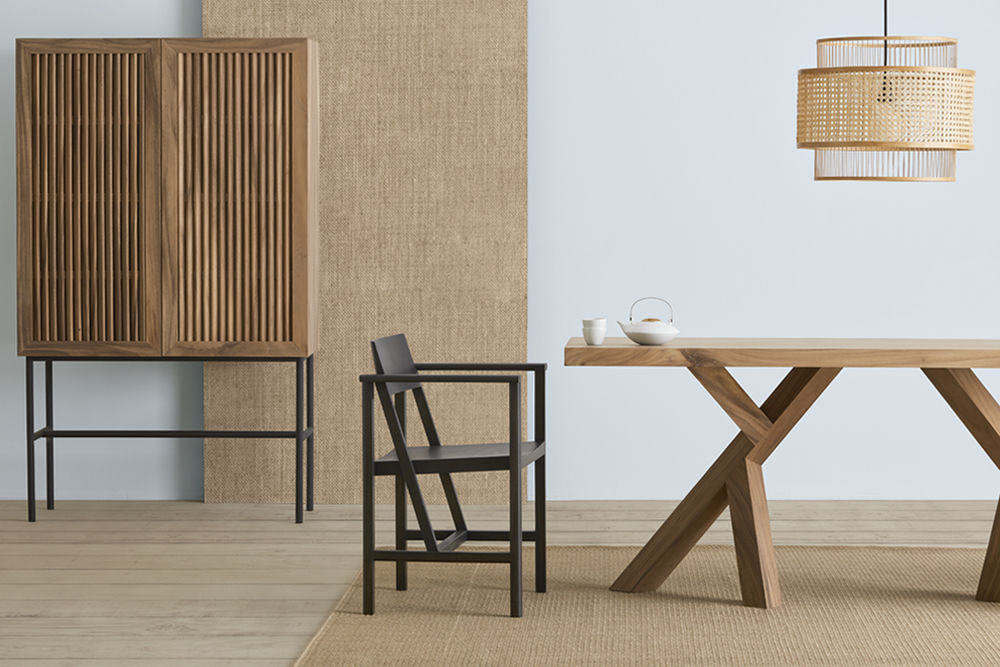 Sala de jantar em madeira com mesa em madeira e cadeira em madeira preta. Luminária de fibras trançadas acima. Estante de ripas de mandeira ao fundo