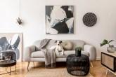 Sala de estar com piso em madeira. Mesa de apoio de fibras pretas em frente com vaso preto ocm planta. Sofá cinza com manta sobre o canto esquerdo e cachorro branco e marrom no centro deitado. Quadro abstrato azul marinho e branco na parede