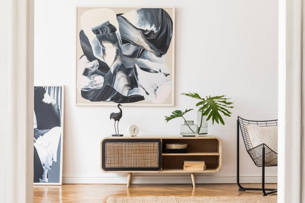 Hack em madeira com costelas de adão em vaso de vidro sobre o tampo. Quadro abstrato azul marinho e branco na parede.