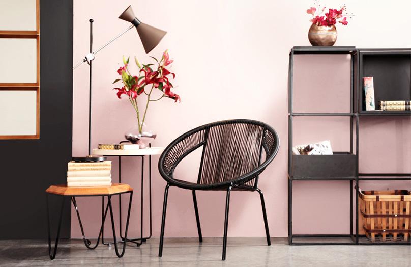 Ambiente com cadeira trançada preta, duas mesas de apoio, uma com flores rosa e a outra com um abajour. Estante preta ao fundo. Parede rosa clara